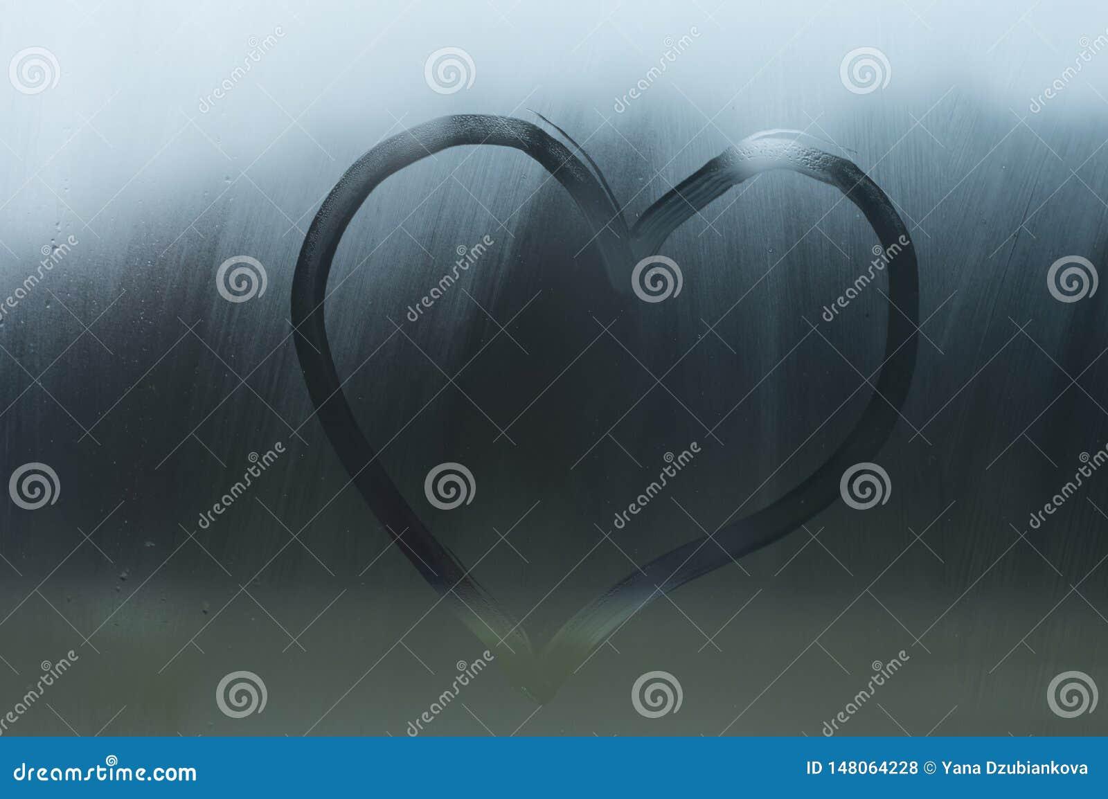 Le coeur d un doigt est dessin? sur la fen?tre a su? Le coeur est peint sur le verre ou sur un miroir