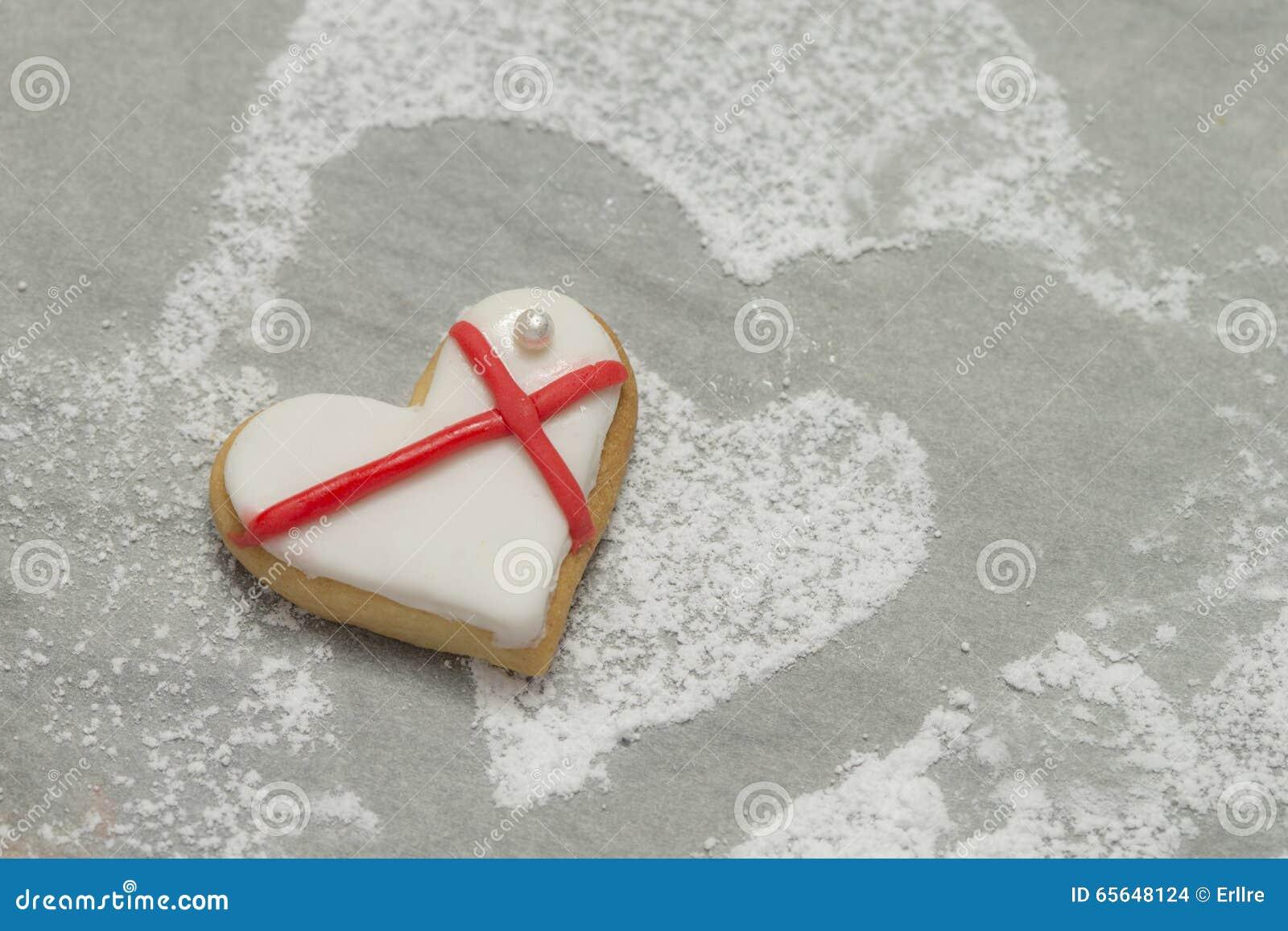 Le coeur de la valentine cuite au four avec le glaçage blanc et rouge