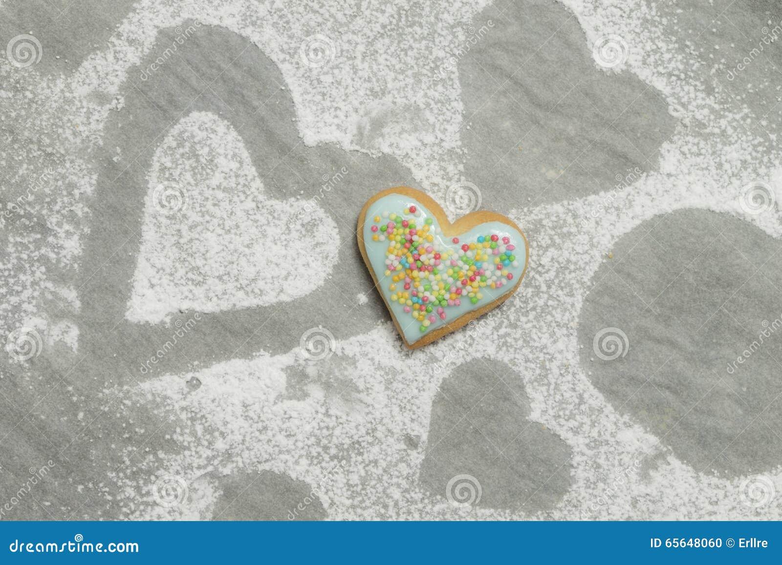 Le coeur de la valentine cuite au four couvert de glaçage et de confettis bleus