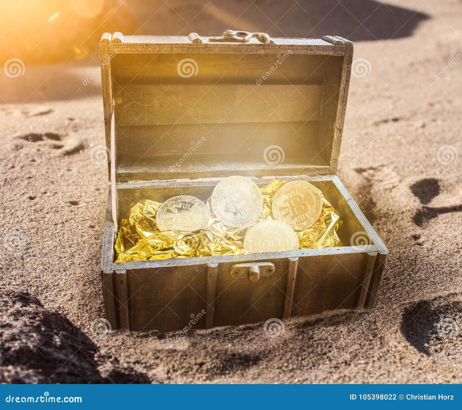Le coffre au trésor rempli de bitcoins entourés par lueur d or burried partiellement en sable
