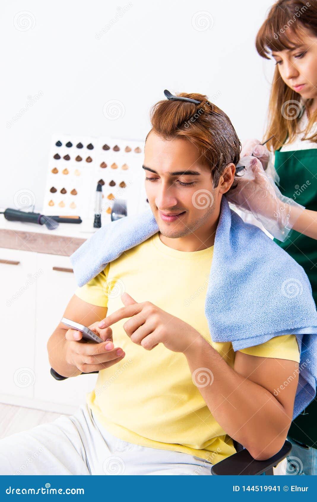 Le coiffeur de femme appliquant le colorant pour équiper des cheveux