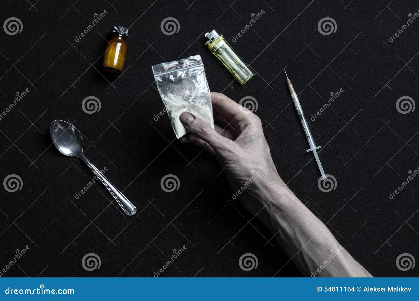 Le combat contre des drogues et le sujet de toxicomanie : les mensonges d intoxiqué de main sur une table foncée et autour de ell