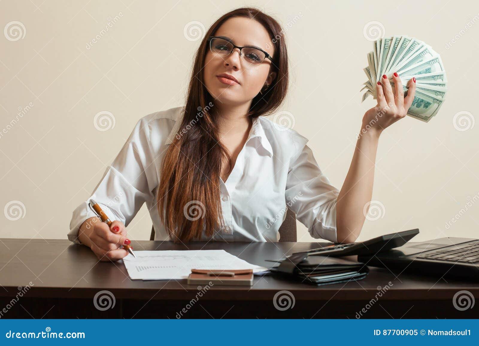 Le comptable féminin tenant des dollars éventent dans sa main