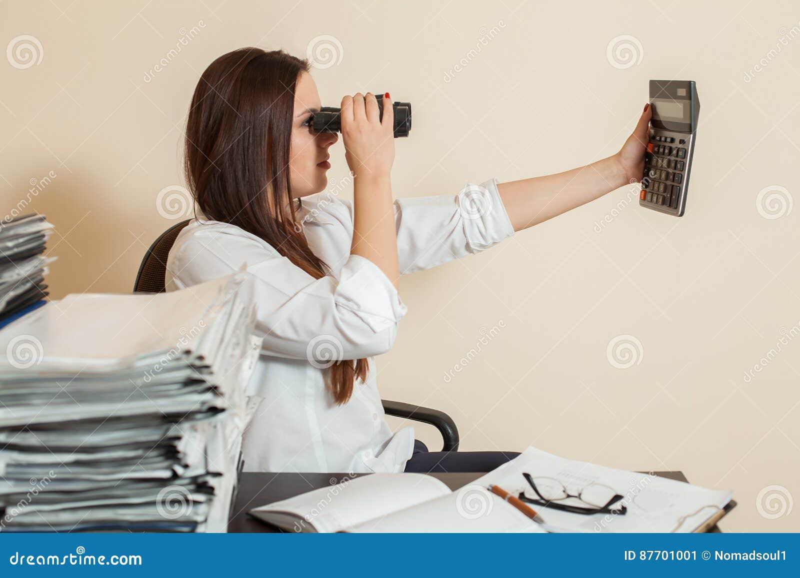 Le comptable regarde par des jumelles sur la calculatrice