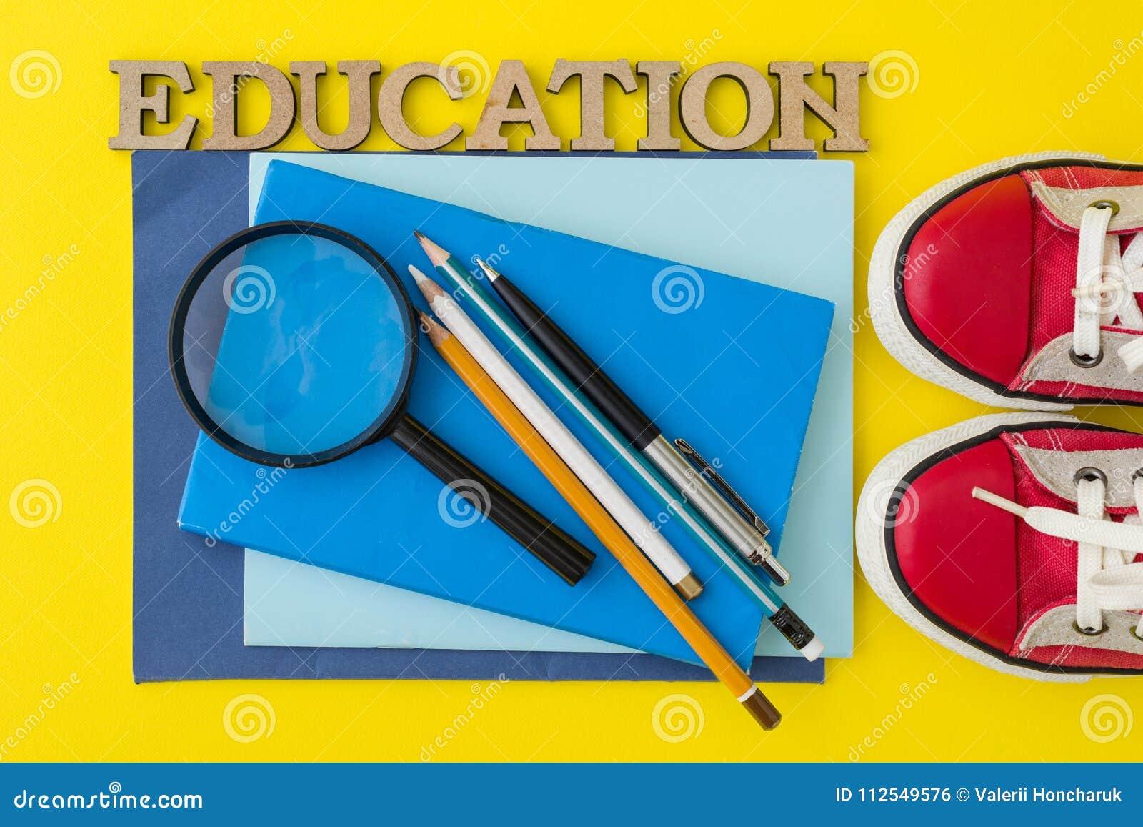 Le concept de l éducation Espadrilles rouges, fournitures scolaires, livres, carnets avec le fond jaune