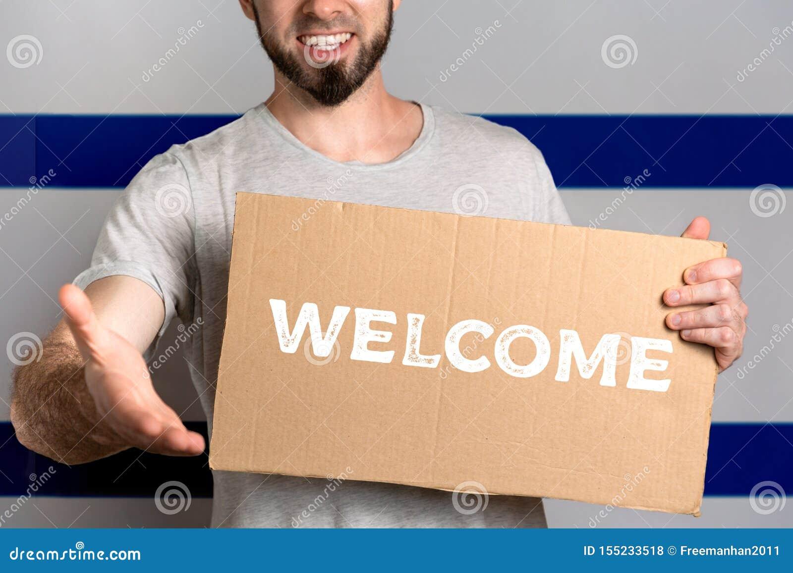 Le concept de la tolérance pour des immigrés et des personnes de différentes positions de la vie Un homme tient un carton et étir