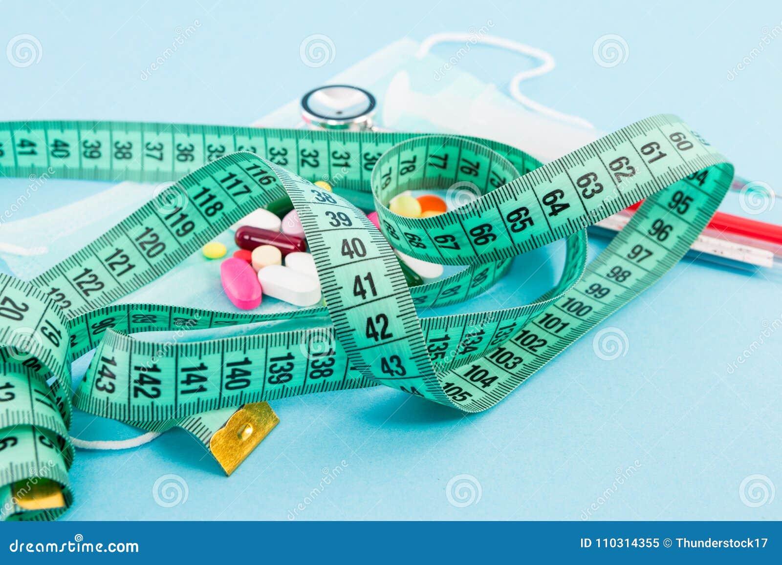 Le concept de régime et suivant un régime de centimètre attachent du ruban adhésif et des pilules