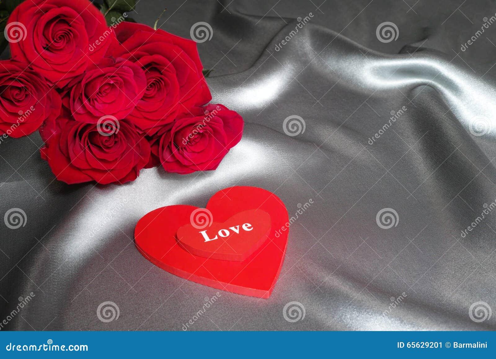 Le concept de Saint-Valentin, concept de fête des mères, les roses rouges sur le fond gris en soie avec les coeurs rouges aiment
