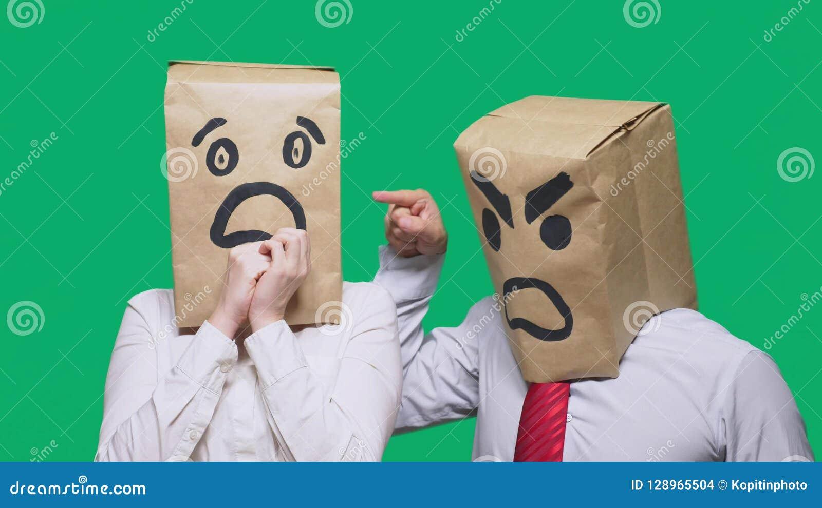 Le concept des émotions et des gestes Deux personnes dans des sacs en papier avec des sourires Le smiley agressif jure
