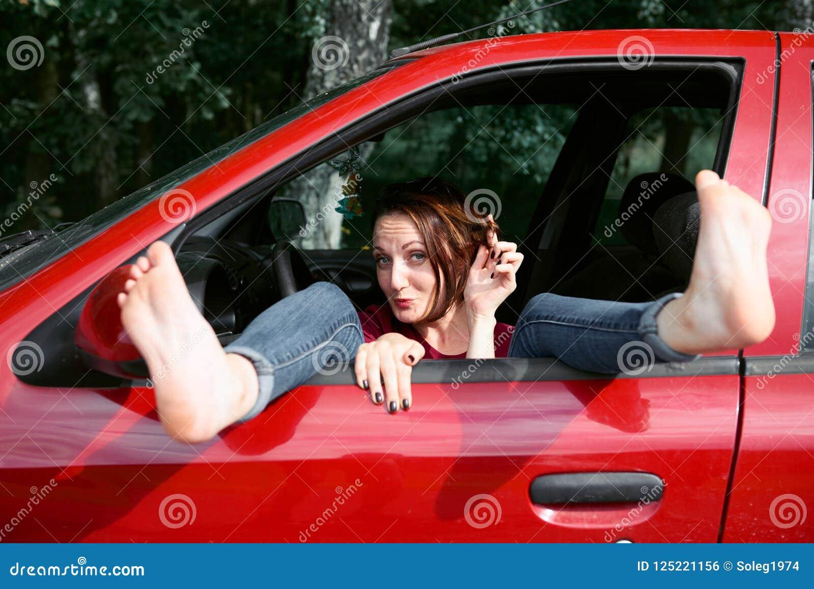 Le conducteur de jeune femme se reposant dans une voiture rouge, a mis ses pieds sur la fenêtre de voiture et flirter, concept he
