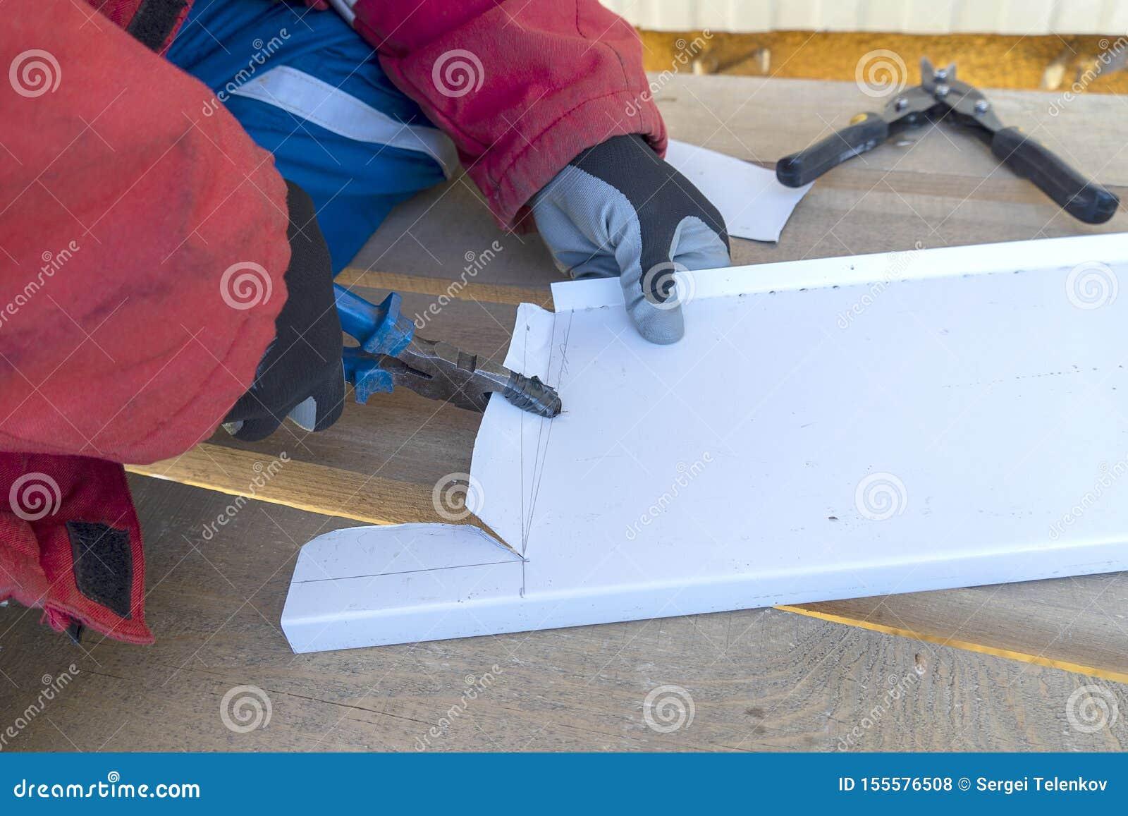 Le constructeur avec des pinces plie une feuille de métal La main d un travailleur plie le fer de toit avec un outil de pinces av