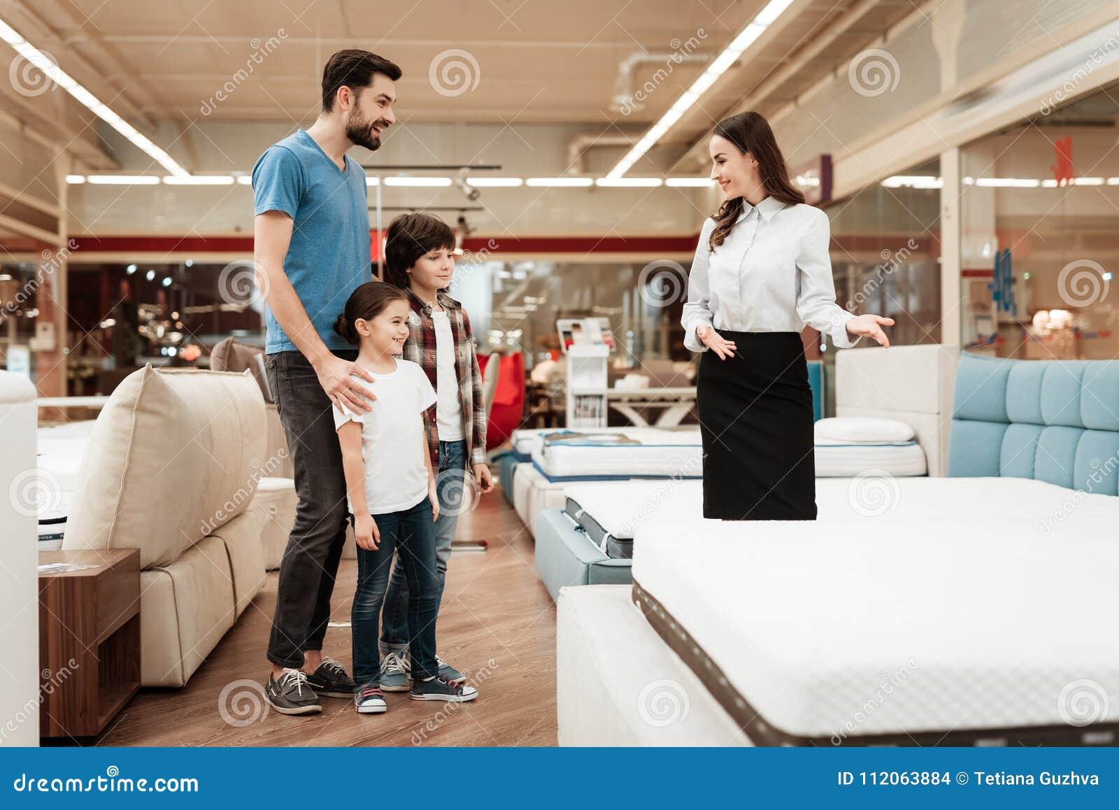 Le consultant en matière de jeune fille démontre le matelas orthopédique au jeune père avec des enfants dans le magasin de meuble