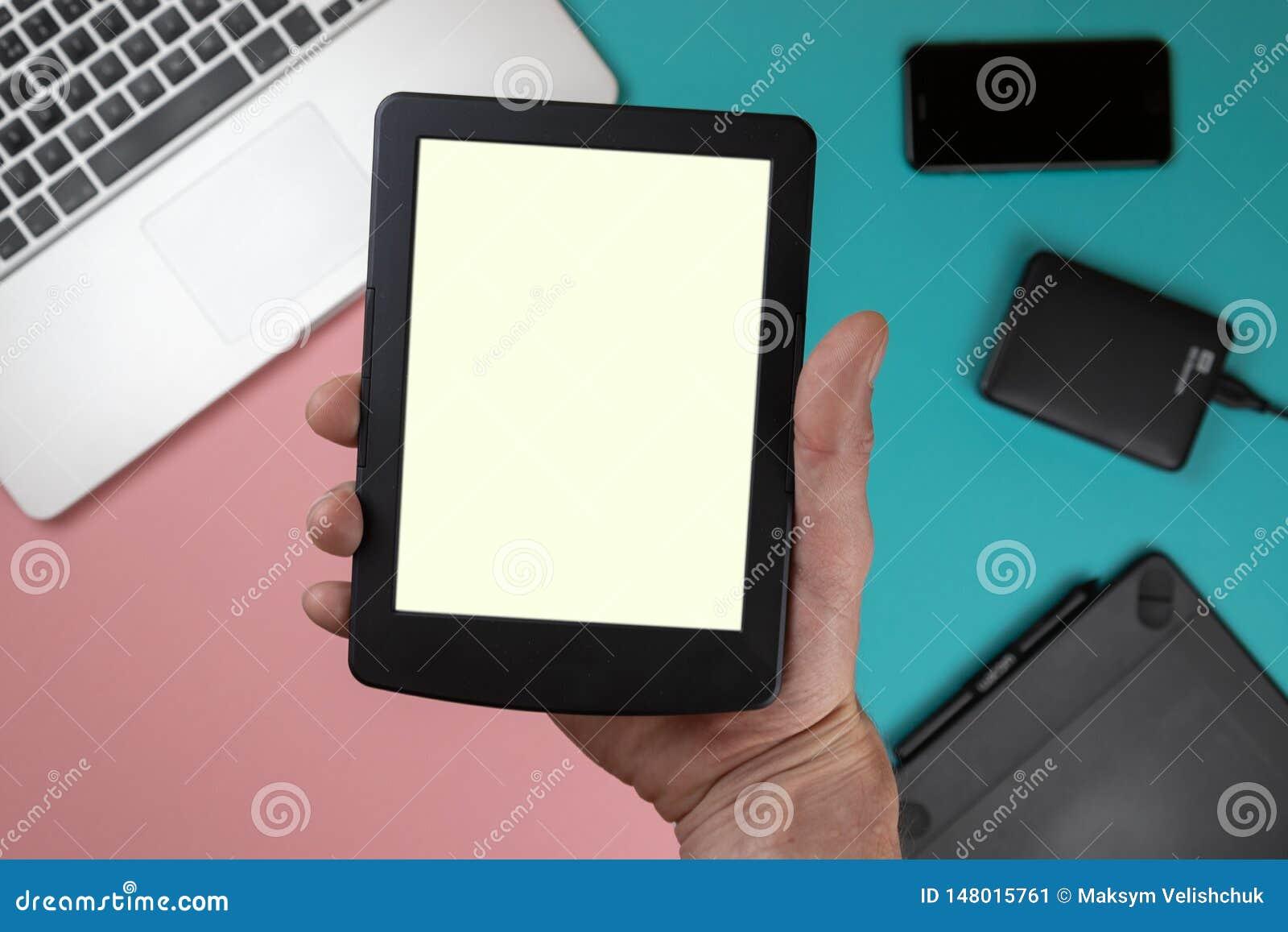 Le contact de main sur l écran vide du comprimé au-dessus de la vue supérieure colorée de table, laissent l espace pour l afficha