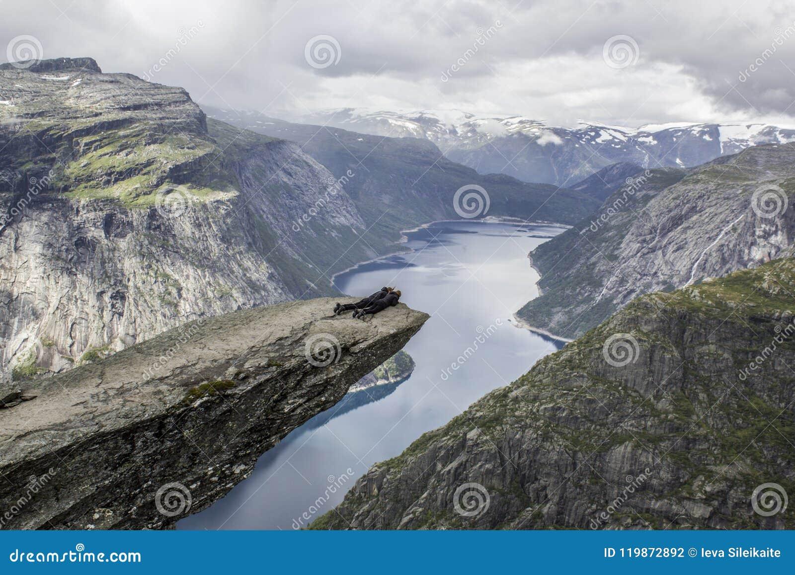 Le coppie che si riposano sulla lingua del ` s del troll di trolltunga oscillano, la Norvegia