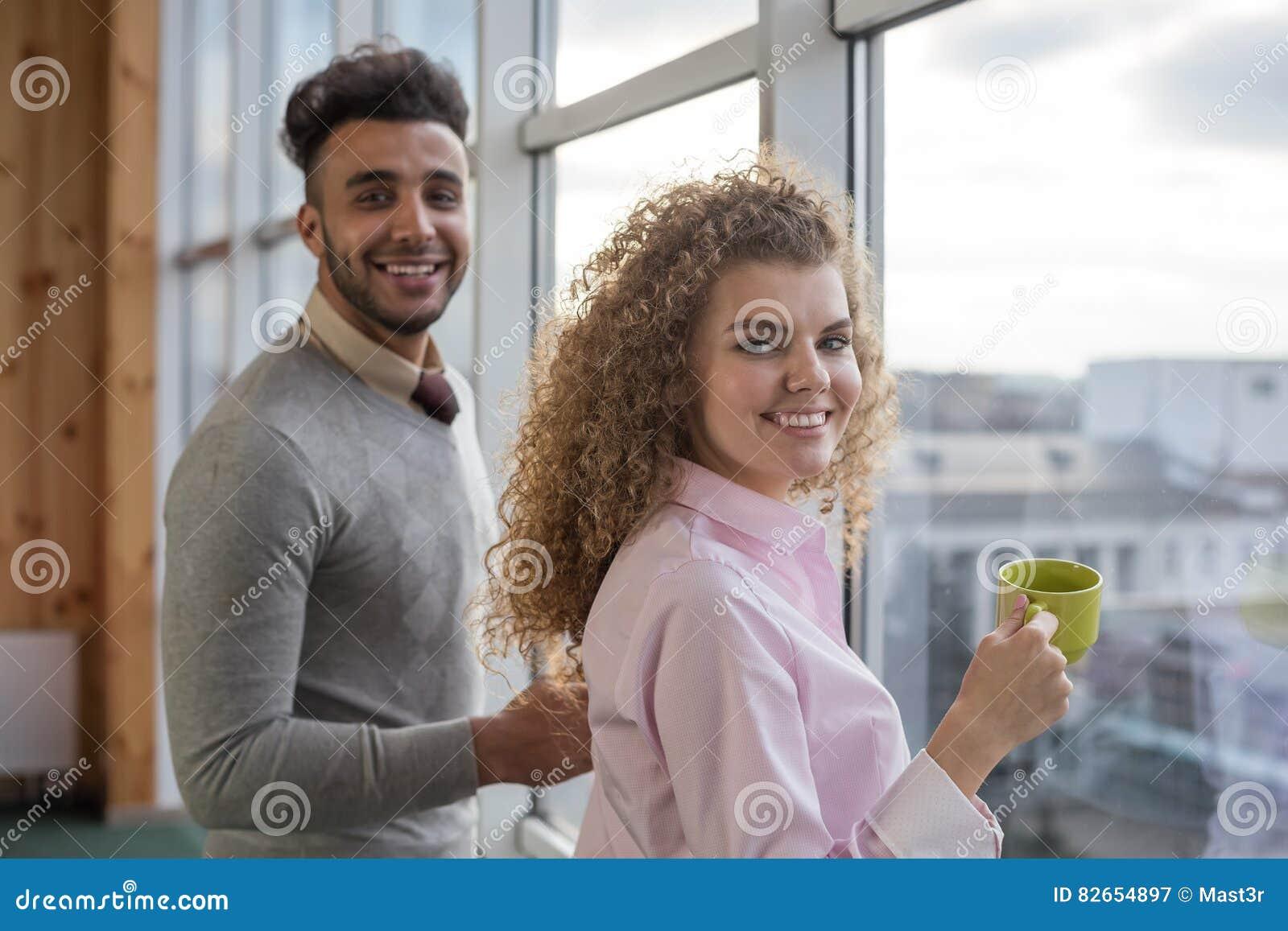 Le coppie delle persone di affari tengono la pausa caffè delle tazze nei colleghe del centro di Coworking che stanno nella finest