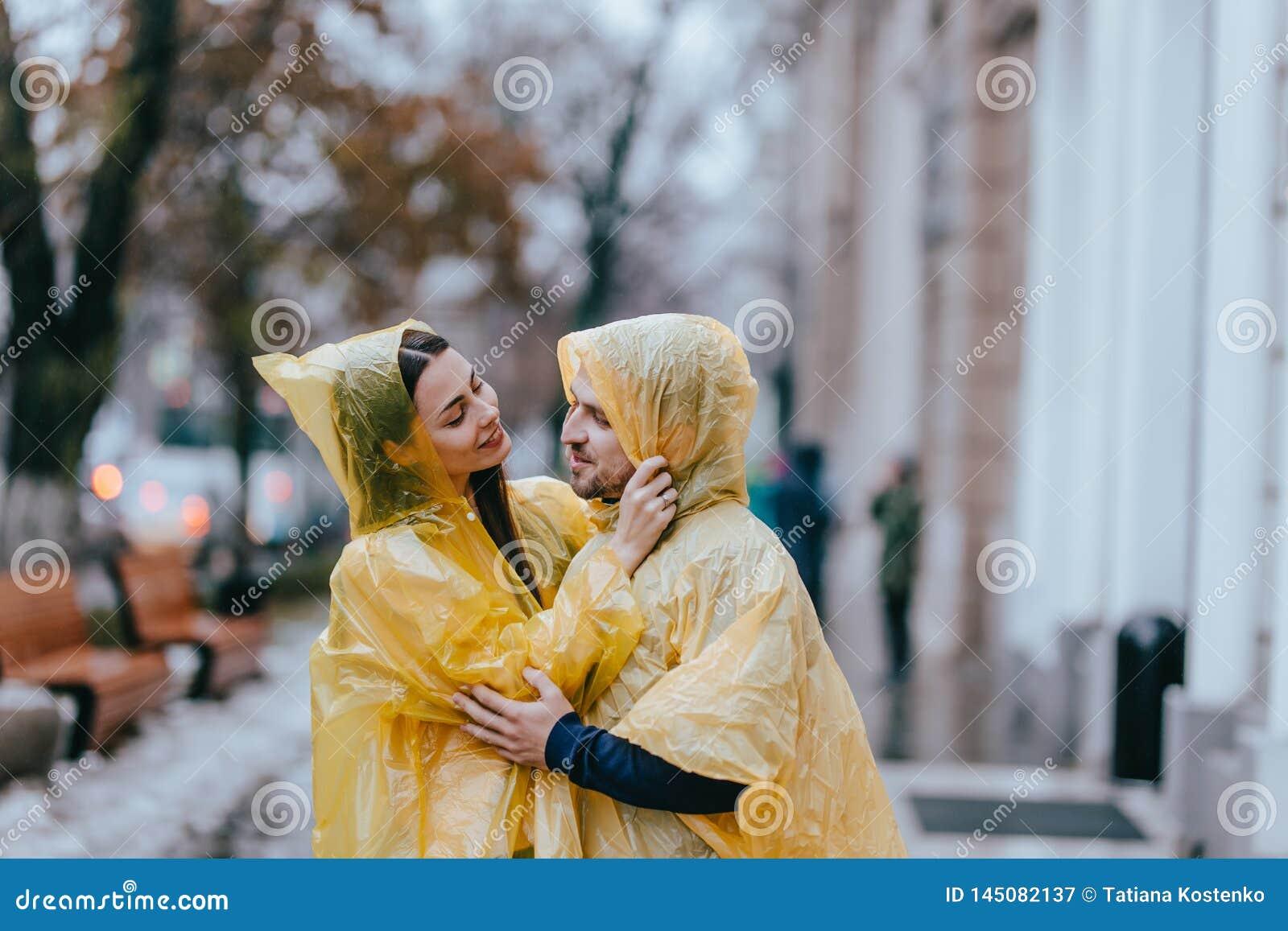 Le coppie di amore, il tipo e la sua amica vestiti in impermeabili gialli stanno abbracciando sulla via nella pioggia