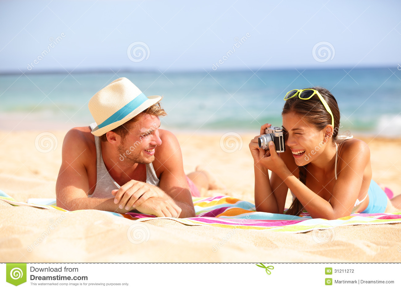 Le coppie di divertimento della spiaggia viaggiano - donna che prende la foto