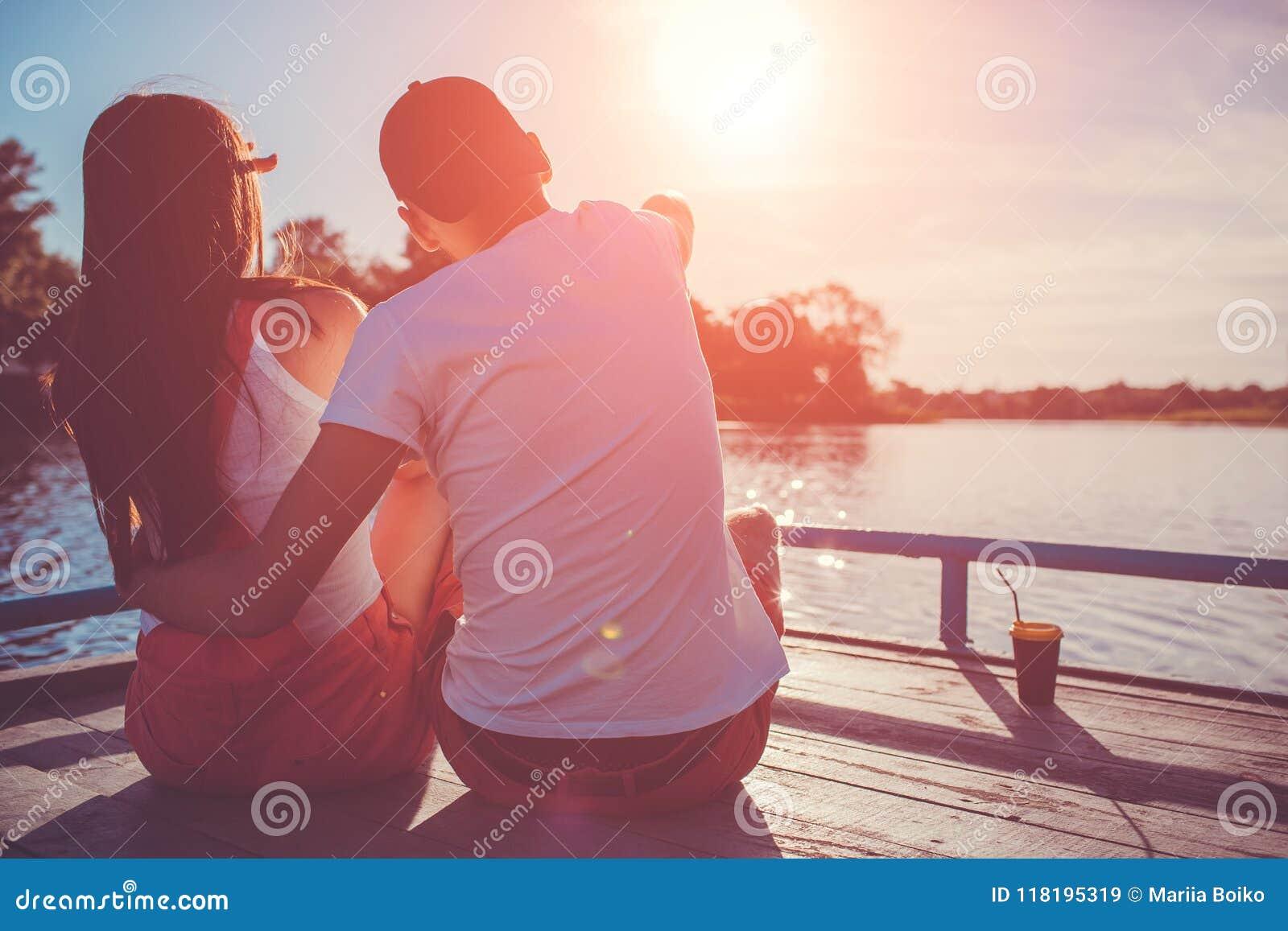 Le coppie felici nell amore che abbraccia sul fiume si mettono in bacino al tramonto Giovani che raffreddano dall acqua
