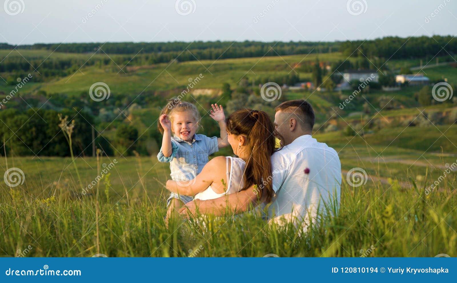 Le coppie incinte con la figlia del bambino fanno il tempo libero appoggiare all aperto la vista