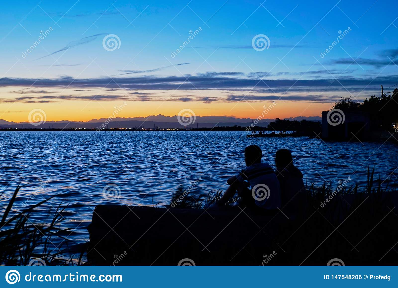Le coppie nell amore contemplano il tramonto nel Albufera di Valencia