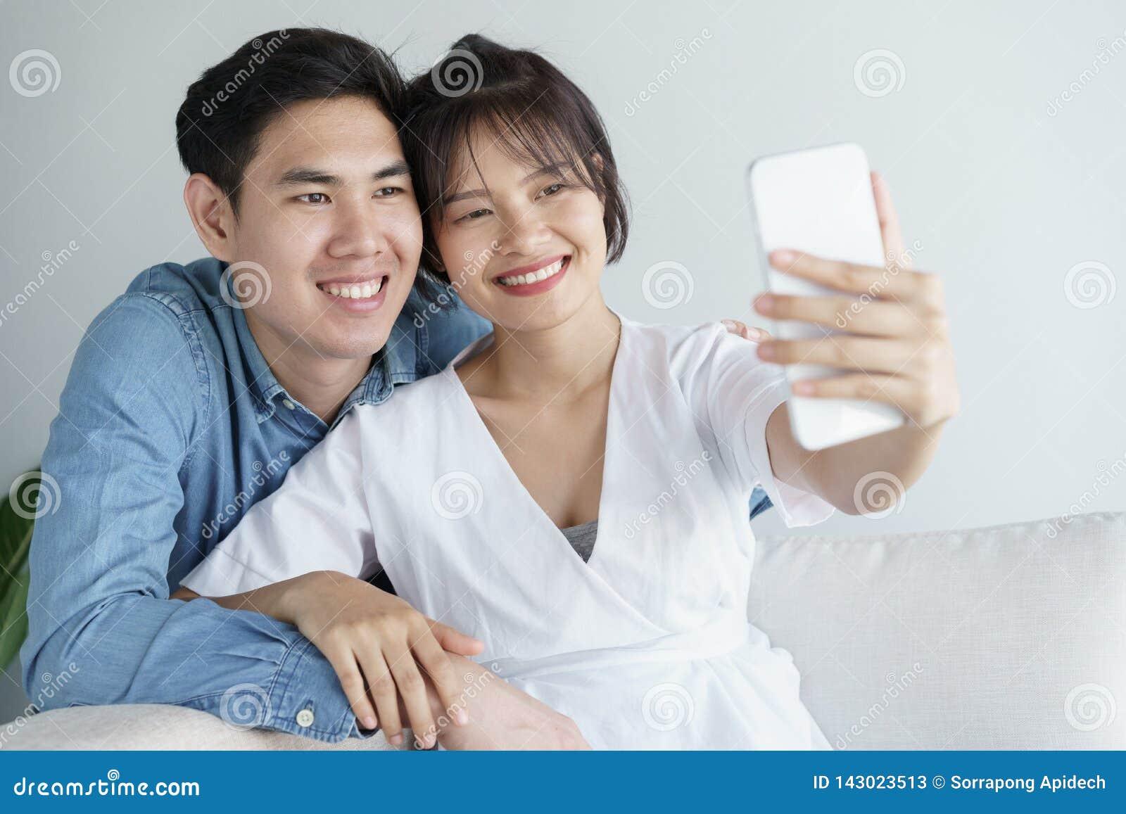 Le coppie sveglie nell amore sono abbraccianti e sedentesi sul sofà Sono selfie di mattina all interno a casa, indossando le attr