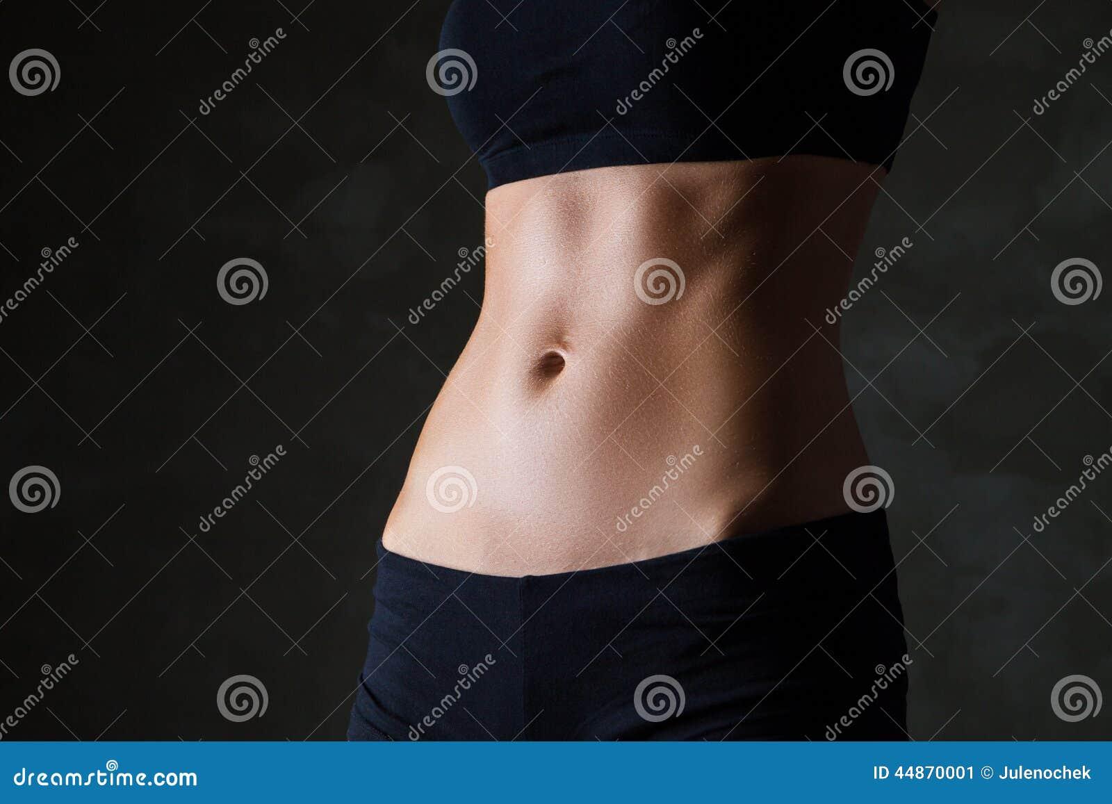Le corps de la femme mince au-dessus du fond gris-foncé