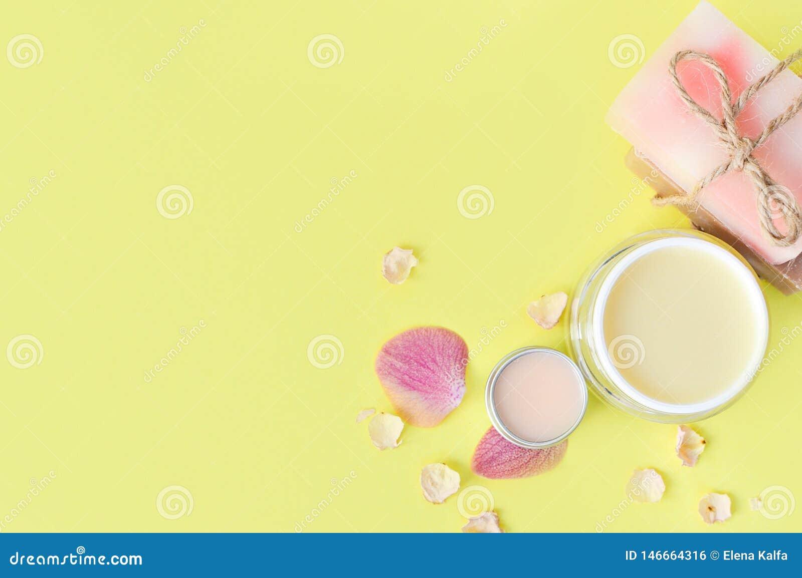 Le cosmétique écrème, balt de lèvre sur un fond jaune Soin de beaut? de station thermale L espace pour un texte Copiez l espace C