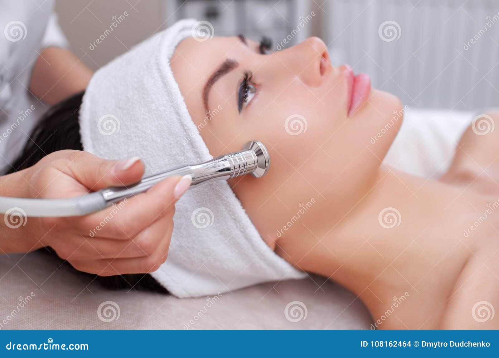 Le cosmetologist fait la procédure Microdermabrasion de la peau faciale d un beau, jeune femme dans un salon de beauté