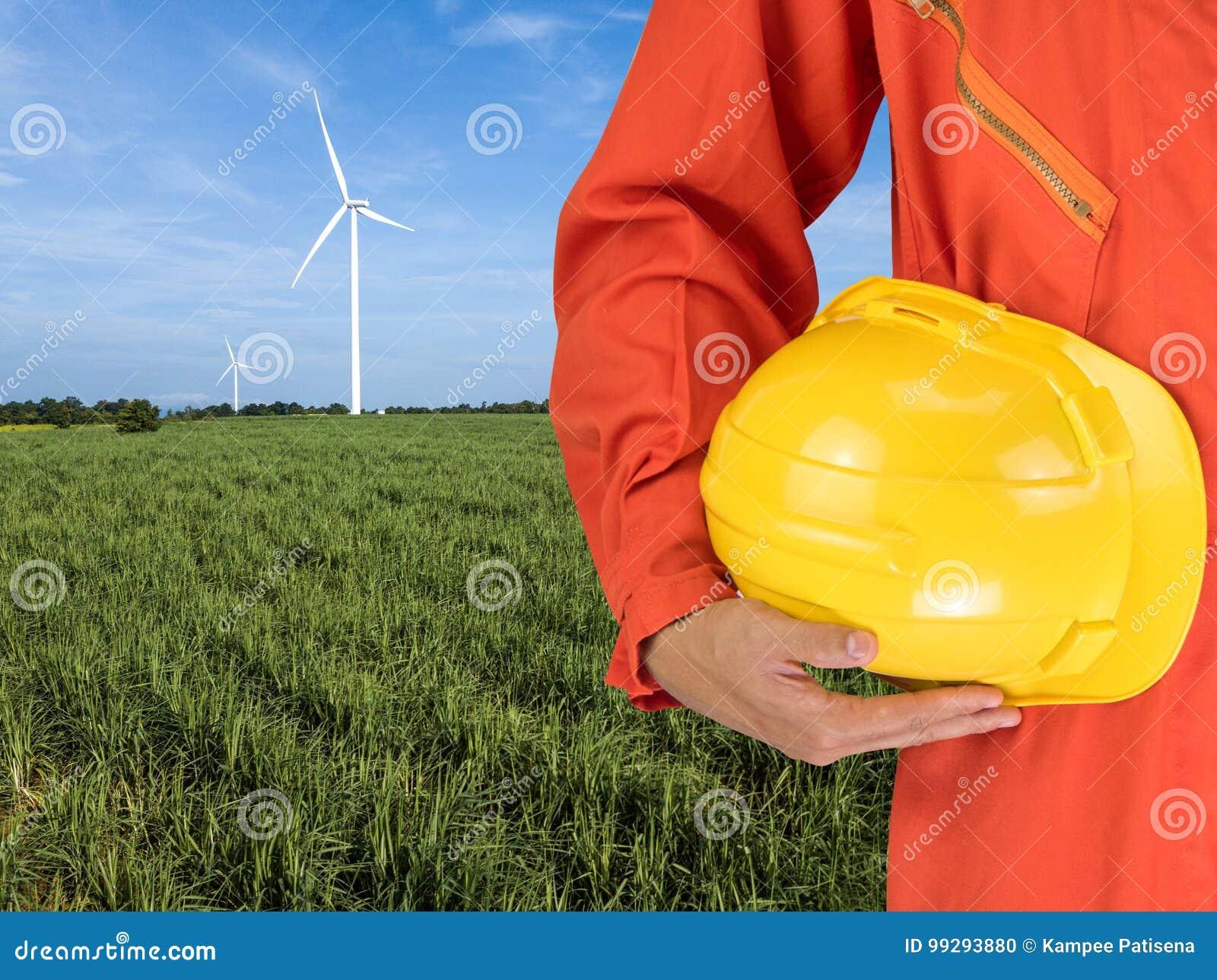 Le costume et la main de sécurité tiennent le casque jaune avec le gener de turbines de vent