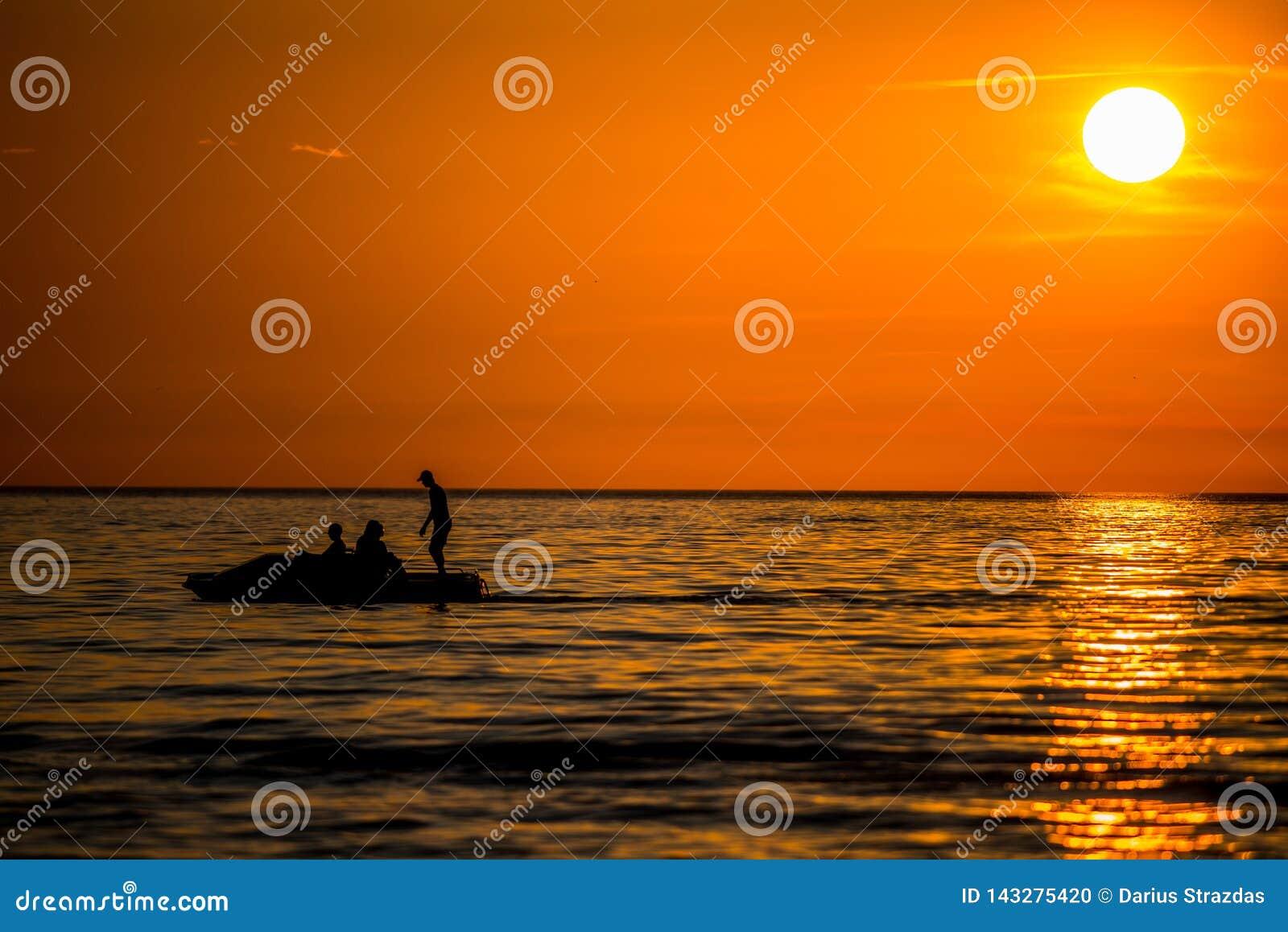 Le coucher du soleil orange, les gens silhouettent avoir l amusement