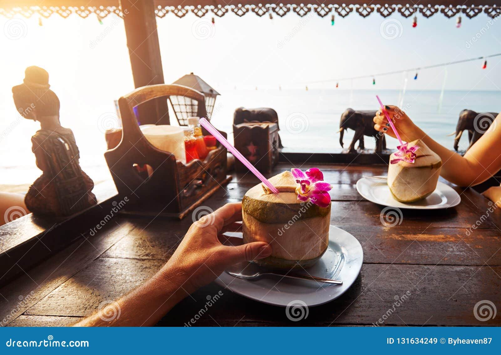 Le couple boit les noix de coco fraîches douces