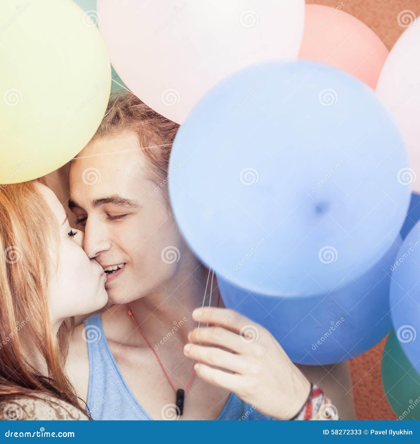 Le couple heureux et drôle embrassant au fond de couleur monte en ballon