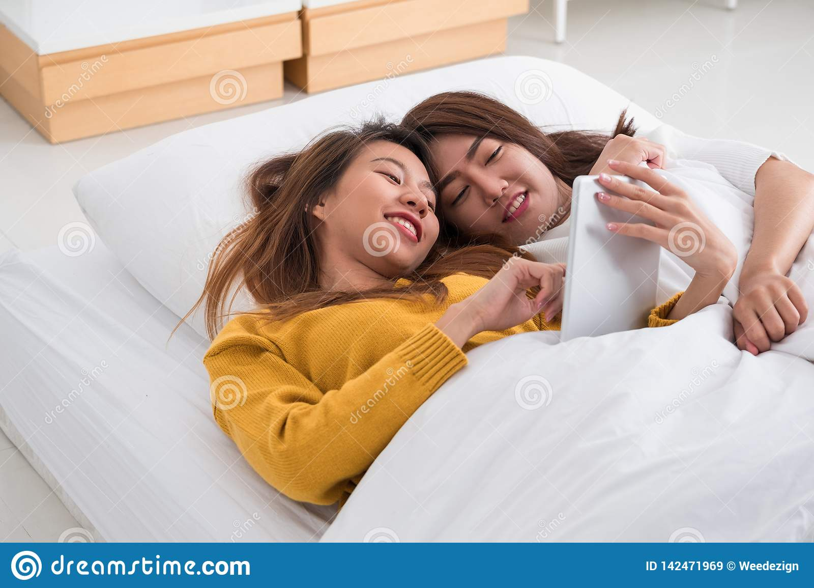 Le couple lesbien asiatique de lgbt se situant sur le lit utilisant la tablette ensemble dans la chambre à coucher avec le moment