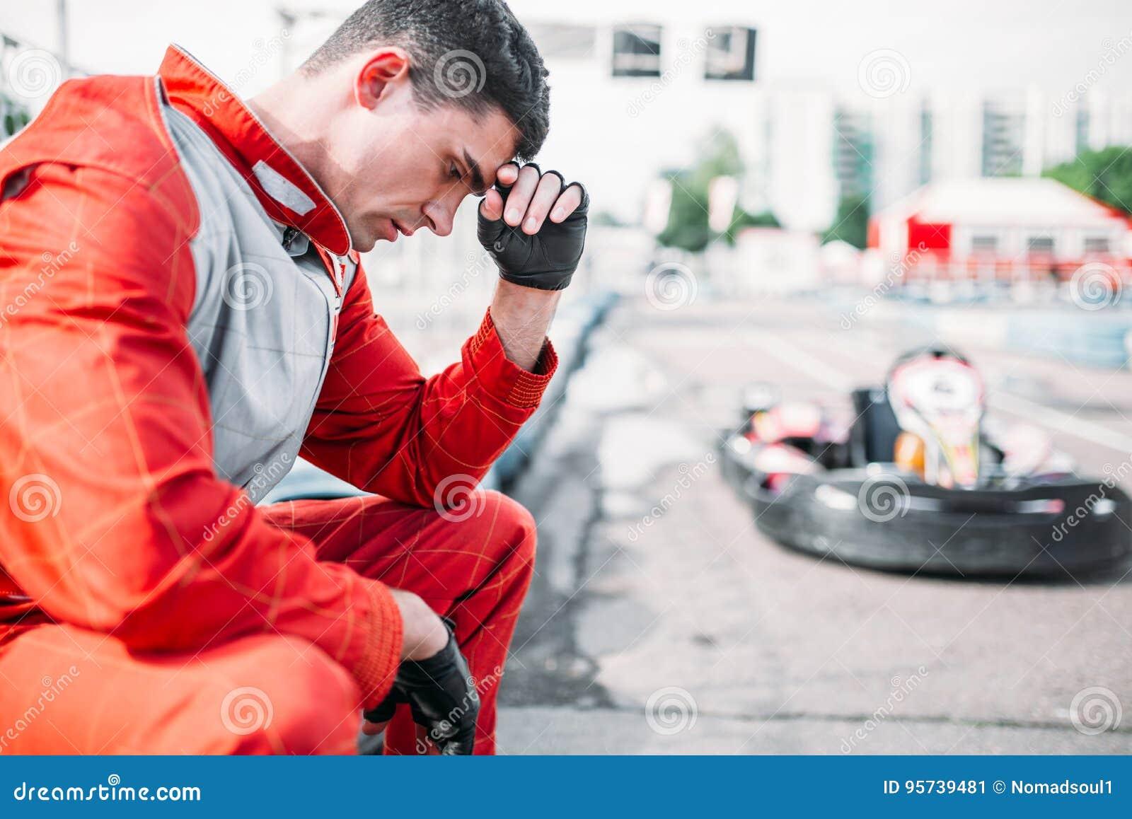 Le coureur de Karting s assied sur un pneu, voie extérieure de kart