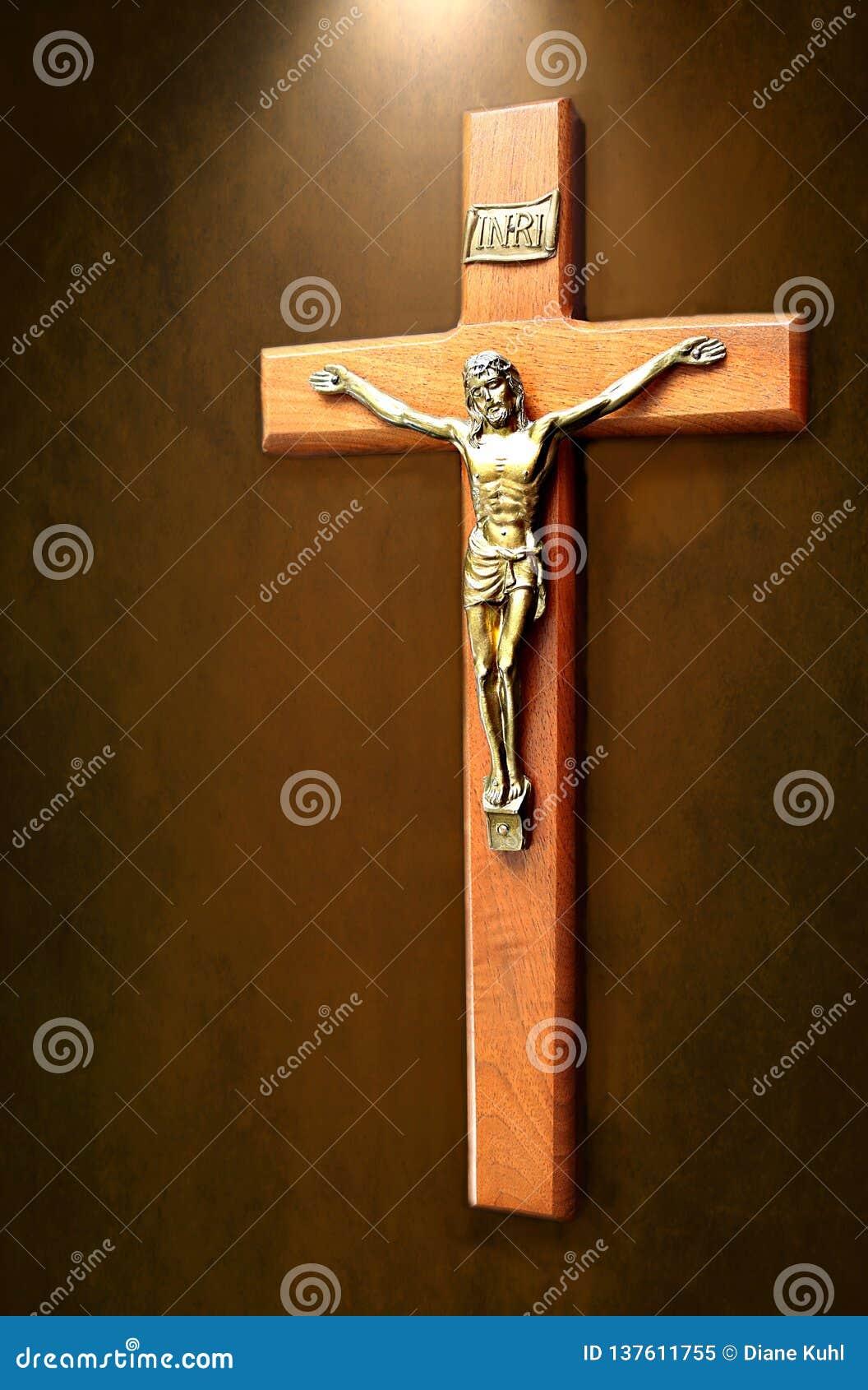 Le crucifix avec la lumière brillant là-dessus a isolé sur le fond chiné brun
