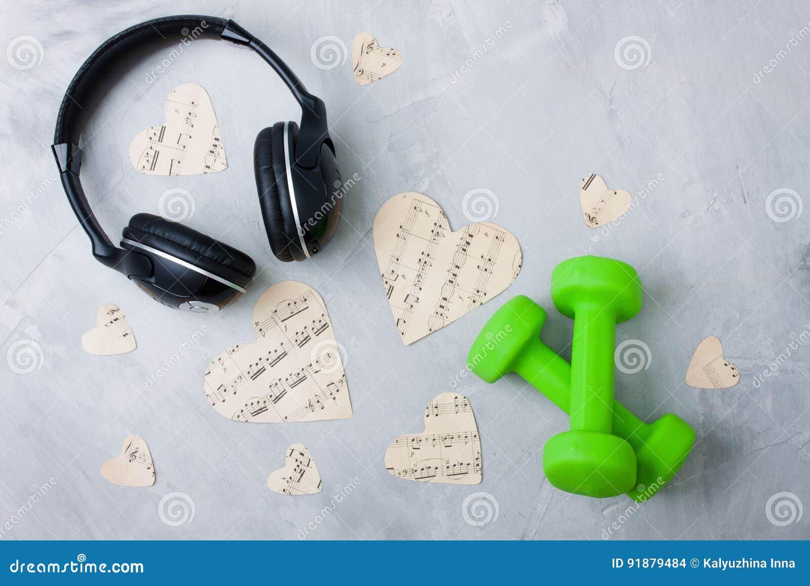 Le cuffie della composizione in musica di sport di Flatlay incartano la testa di legno dei cuori