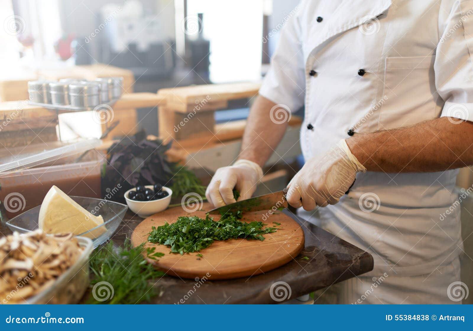 Le cuisinier coupe le persil avec un couteau à bord