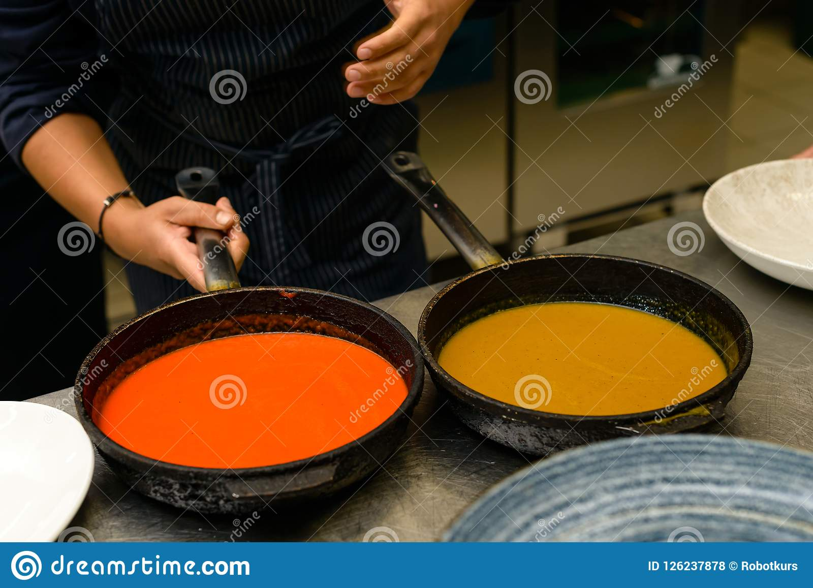 Le cuisinier de chef prépare une sauce chaude dans la poêle pour un repas délicieux dans le restaurant de cuisine