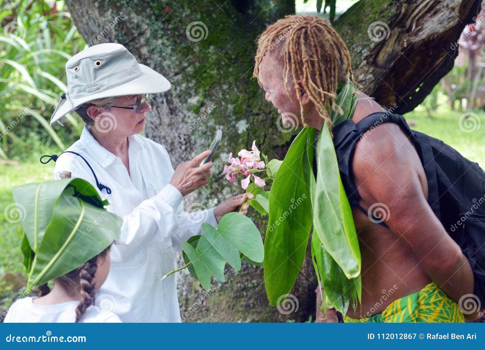 Le cuisinier Islander explique à l les touristes occidentaux au sujet des gens du pays nationaux