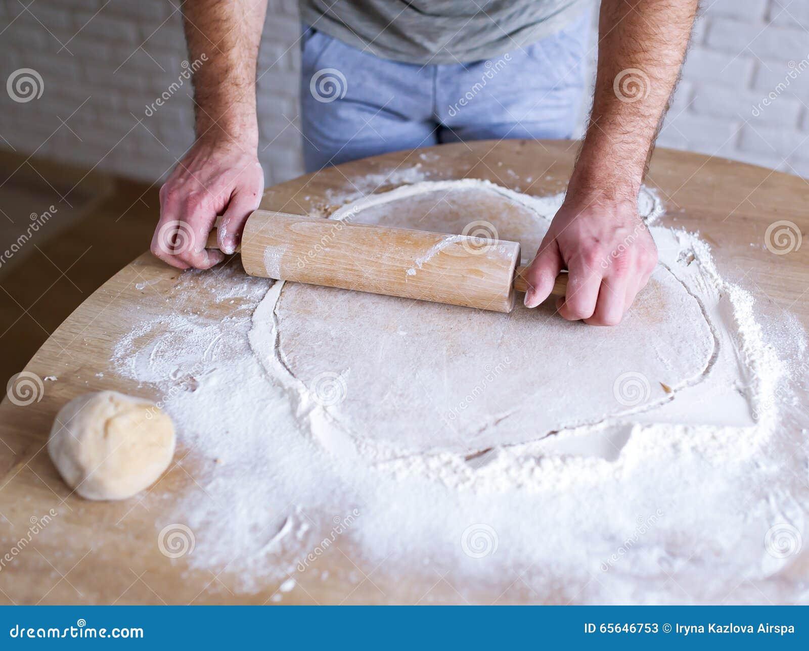 Le cuisinier masculin roule la pâte sur une table