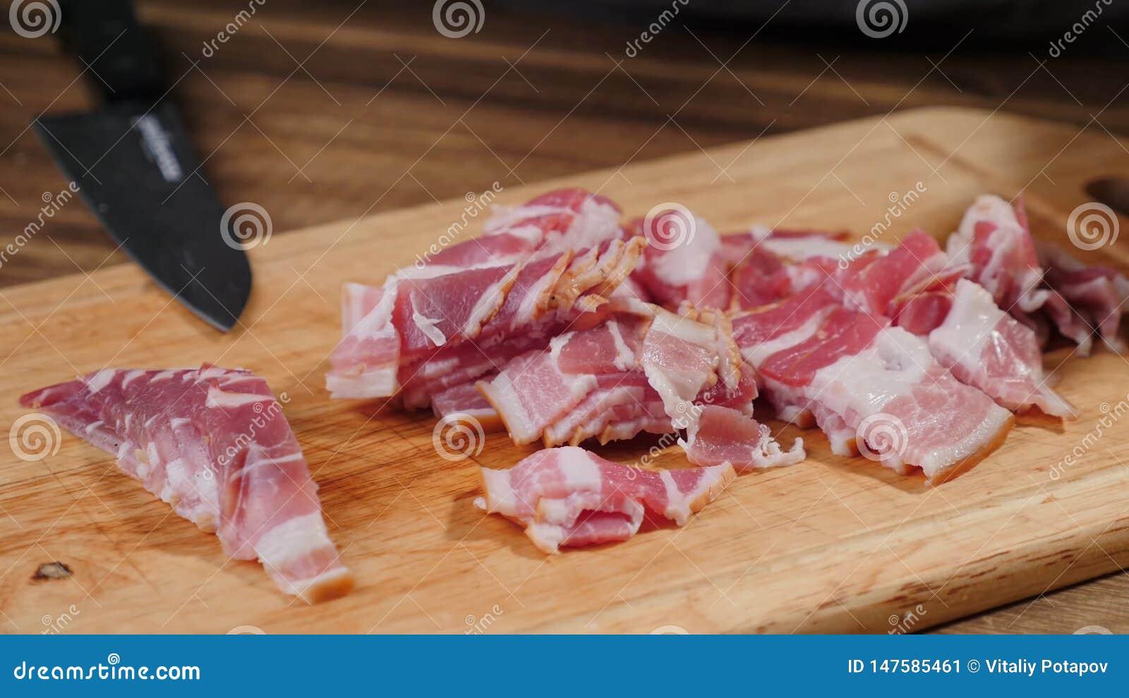 Le cuisinier remet le lard de d?coupage Nourriture, tranche