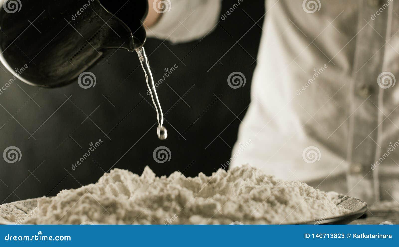 Le cuisinier verse l eau sur la farine de la cruche dans la cuisine