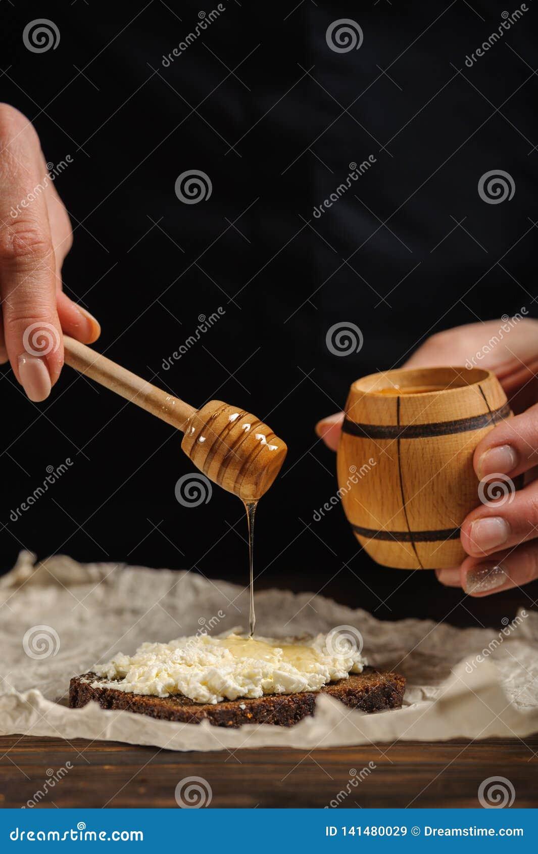 Le cuisinier verse le miel sur le pain