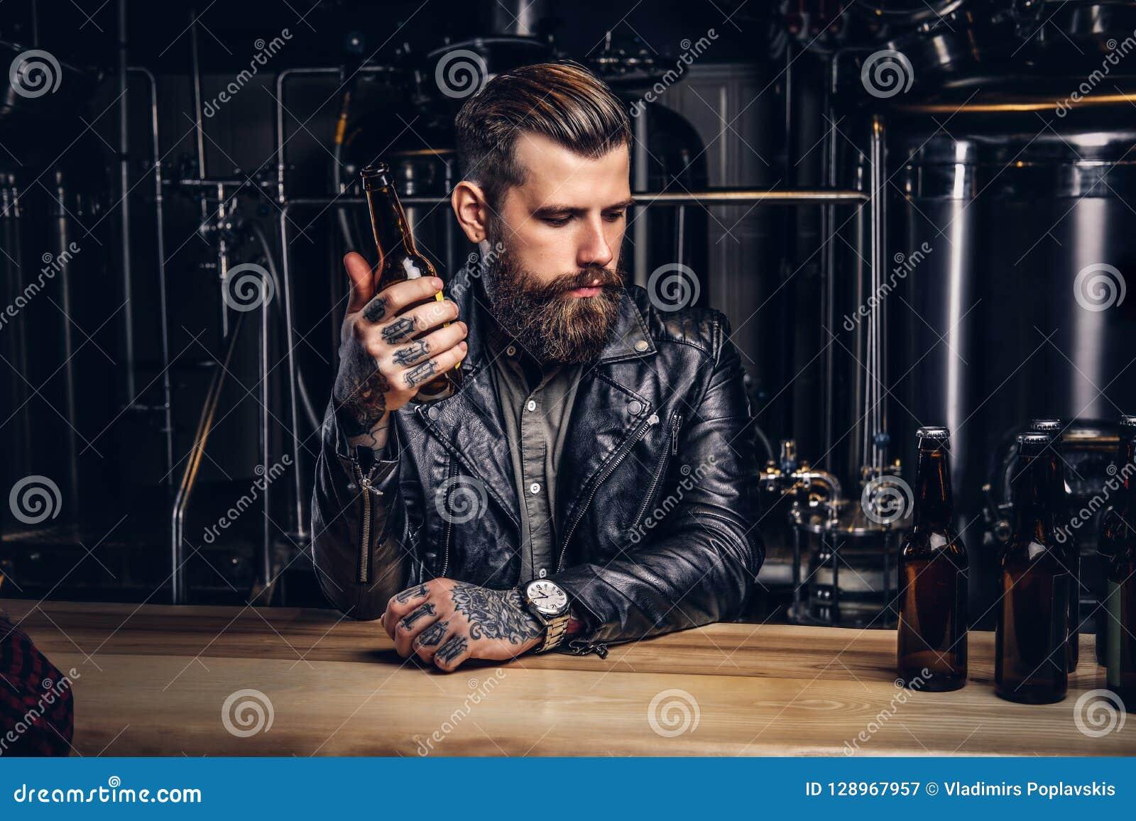 Le cycliste barbu élégant a habillé la veste en cuir noire se reposant au compteur de barre dans la brasserie indépendante