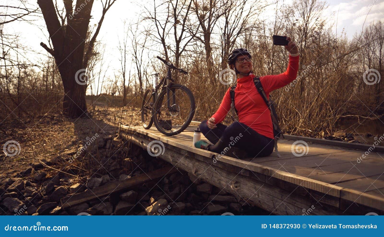 Le cycliste caucasien heureux de femme fait ? une photo d elle-m?me un selfie au t?l?phone tout en se reposant sur le pont au-des