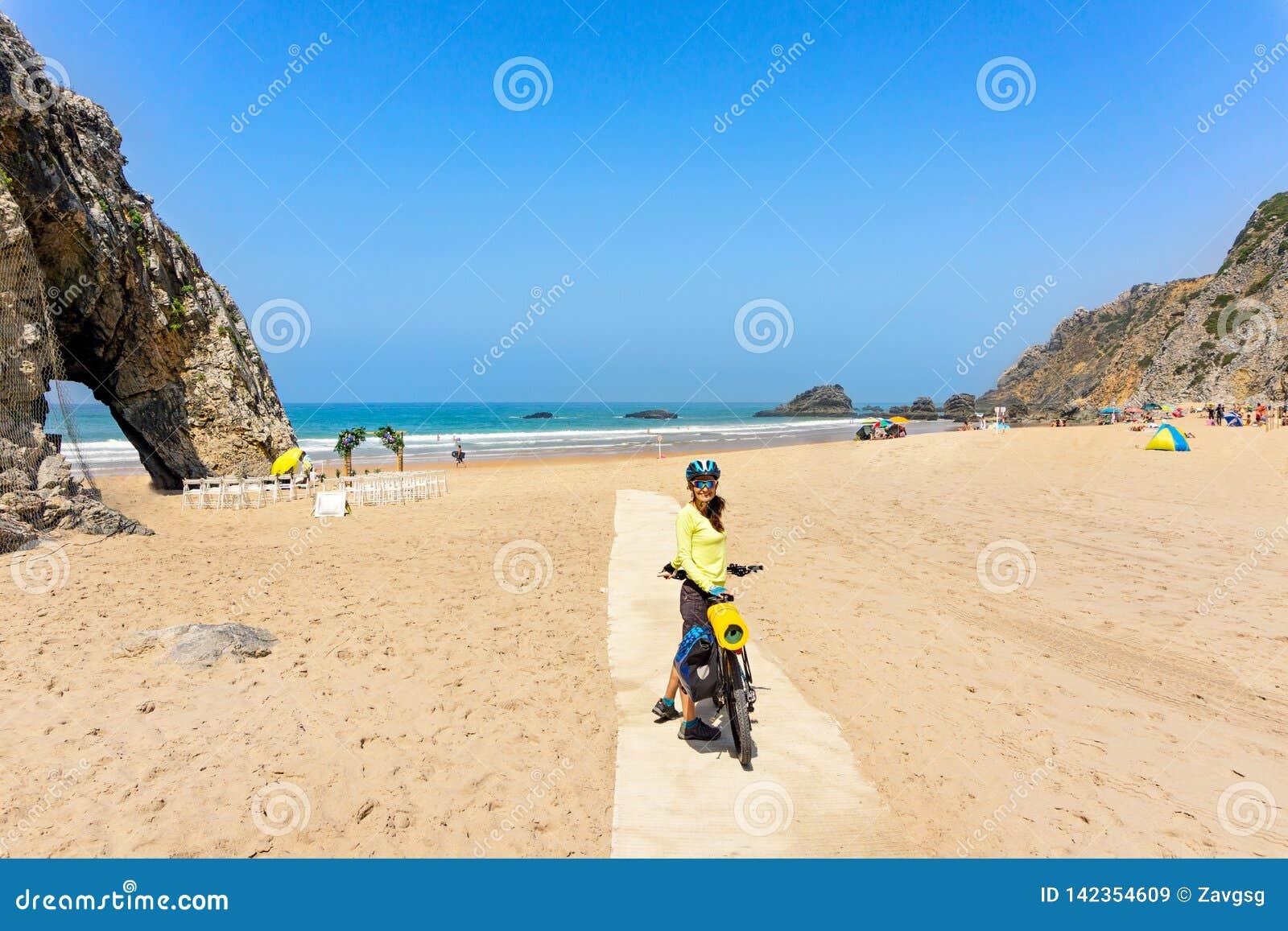 Le cycliste féminin attirant adulte avec son vélo est posant et souriant sur une plage d océan Le Portugal, l Europe