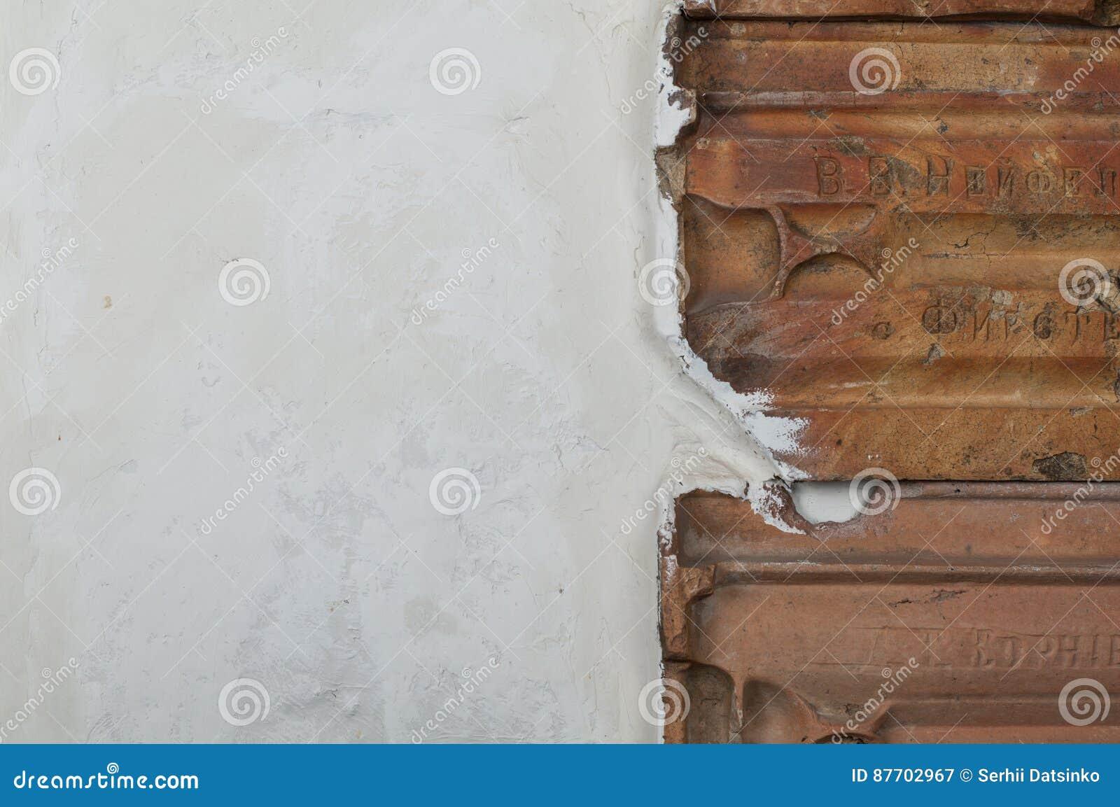 Le détail de la texture sale blanche de mur avec des tuiles de toit stucco des murs et des tuiles de rouge de vintage