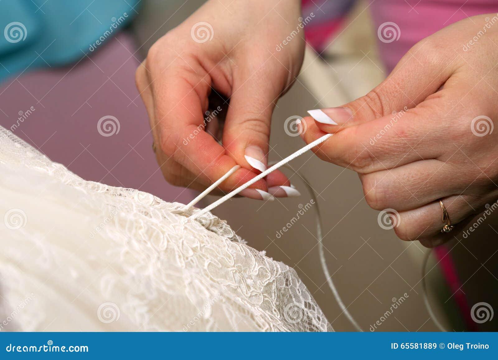 Le damigelle d onore la aiutano a mettere sopra il vestito da sposa