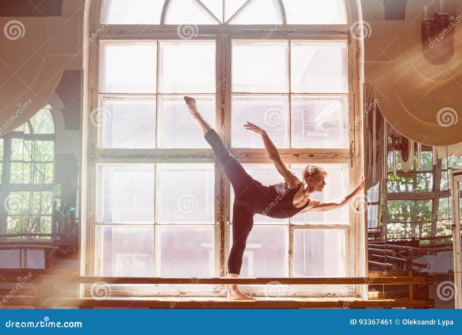 Le danseur classique masculin danse devant une fenêtre