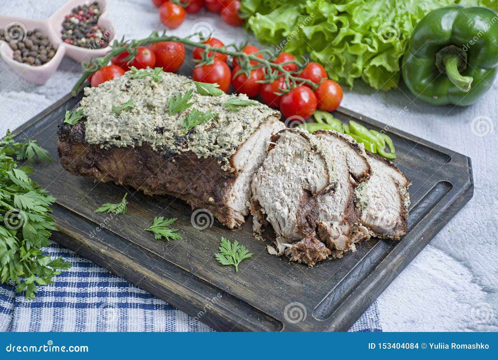 Le de porc cuit au four côtelette dans une noix et une sauce en bon état sur une planche à découper avec les herbes et les légume
